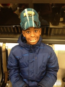 Tavares, 9, anxiously waits at the Flint, MI Amtrak station wearing a Jr. Conductor hat